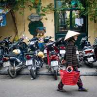 Vietnam, Hanoi. Woman walks in the street of Hanoi Old Quarter.